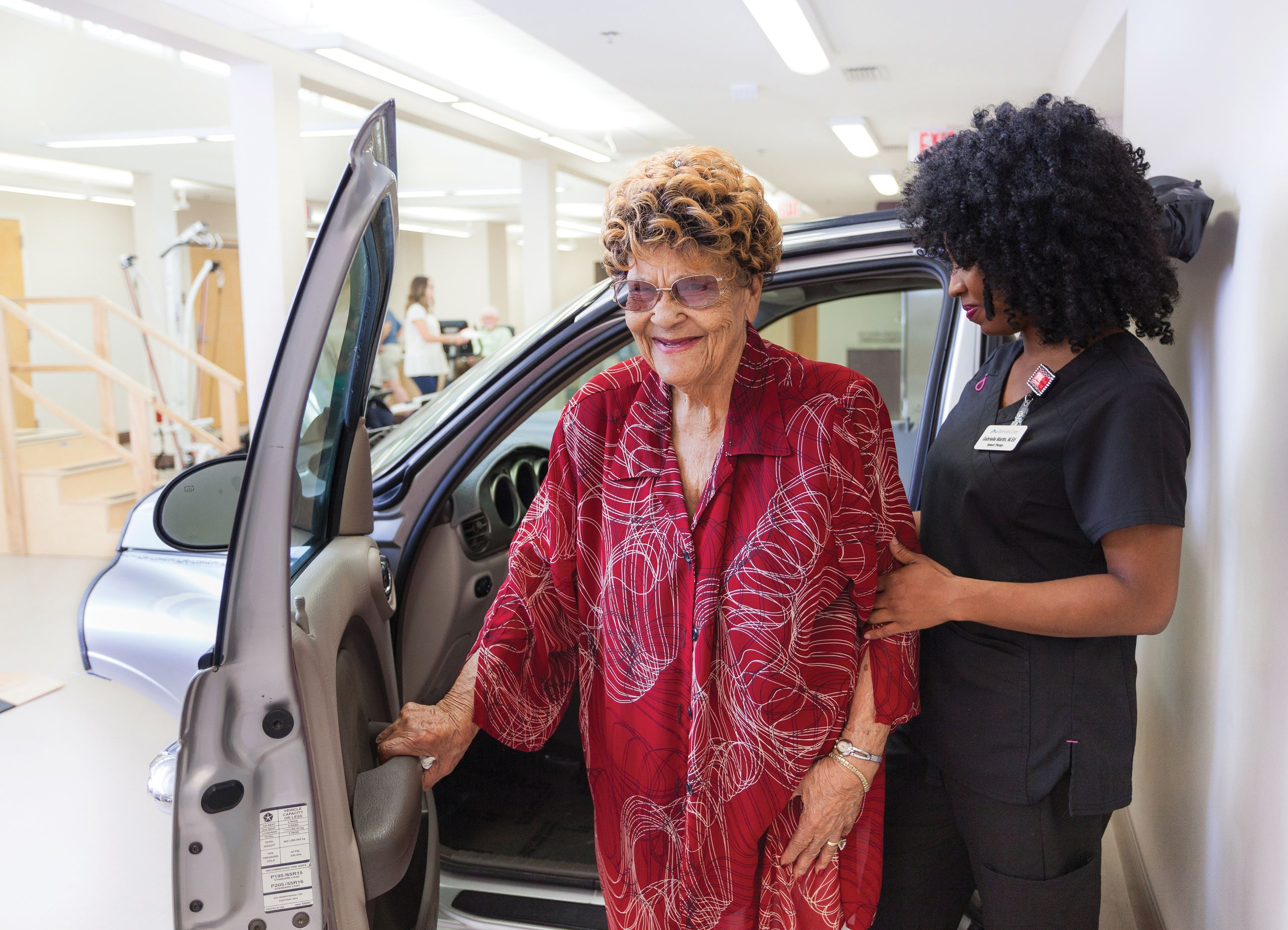 Resident practicing car transfers with a therapist